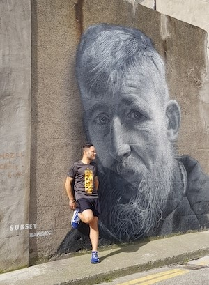 Nick Alexander standing in front of a graffiti painting in a jogging gear.