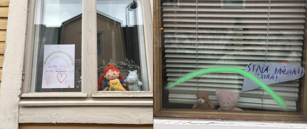 """Tsemppiviestejä sekä hallehaasteen pehmoleluja ikkunoissa. Ensimmäisen kuvan ikkunassa lukee """"Ollaan fyysisesti etäällä, mutta henkisesti lähellä"""" ja toisessa ikkunassa """"Sinä pärjäät"""""""